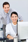 Pretty businesswoman and her colleague working at a computer — Stock Photo