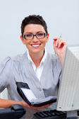Attractive business woman writting on her agenda — Stok fotoğraf