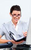 Positive geschäftsfrau, die auf ihre tagesordnung schreiben — Stockfoto