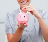 Attractive business woman inserting coin in a piggybank — Stock Photo