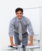 Cheerful businessman leaning on a conference table — Stock Photo