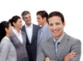 Positive businessman with folded arms standing with his team — Stock Photo