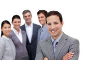 Smiling businessman with folded arms standing with his team — Stock Photo