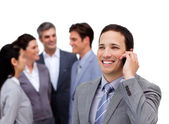 Handsome businessman on phone standing apart from his team — Stok fotoğraf