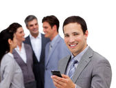Confident businessman and his cellphone standing apart from his — Stock Photo