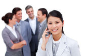 Asian businesswoman and her cellphone standing apart from her te — Stock Photo