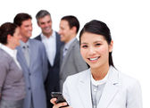 Pretty businesswoman and her cellphone standing apart from her t — Stock Photo