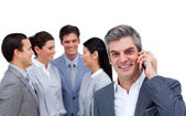 Smiling businessman on phone standing apart from his team — Stock Photo