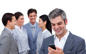 Enthusiastic businessman and his cellphone standing apart from h — Stock Photo