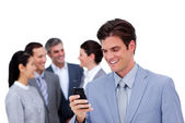 Young businessman and his cellphone standing apart from his team — Stock Photo