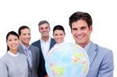 Jonge manager en zijn team houden een terrestrische globe — Stockfoto