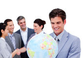 Charismatic manager and his team holding a terrestrial globe — Stock Photo
