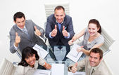 Exuberant business team with thumbs up — Stock Photo