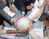 High angle of business team holding a terrestrial globe — Stockfoto