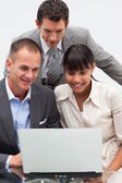 Two businessmen and a businesswoman using a laptop — Stock Photo