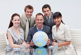 Business team holding a terrestrial globe. Global business — Stock Photo