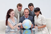 Business team holding a terrestrial globe. International busines — Stockfoto