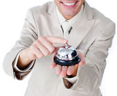 Close-up of a smiling businessman using a service bell — Stock Photo