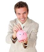 微笑着年轻的商人,在存钱罐存钱 — 图库照片