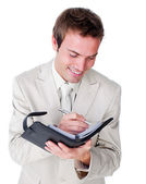 Smiling businessman making notes on his diary — Stock Photo