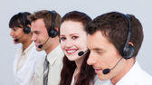 Smiling woman working in a call center with her colleagues — Stock Photo