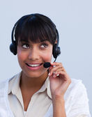 Attractive ethnic businesswoman working in a call center — Stock Photo