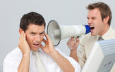 Businessman yelling through a megaphone at his colleague — Stock Photo