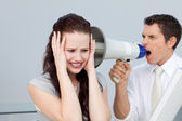 Businessman yelling through a megaphone at a businesswoman — Stock Photo
