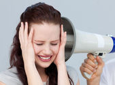 Angry businesswoman listening to a megaphone — Stock Photo