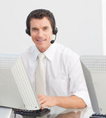 Smiling businessman with a headset on in a call center — Stock Photo