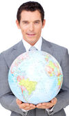 Assertive businessman holding a terrestrial globe — Photo