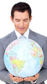 Confident businessman holding a terrestrial globe — Stock Photo