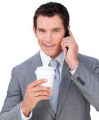 Self-assured businessman on phone holding a drinking cup — Stock Photo