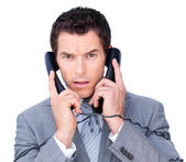 Upset businessman tangle up in phone wires — Stock Photo