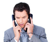 Young businessman tangle up in phone wires — Stock Photo