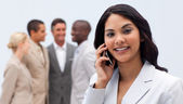 Ethnic businesswoman on phone with her team in the background — Stock Photo
