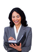 Ethnic businesswoman making notes on her agenda — Stock Photo