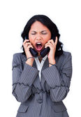 Angry businesswoman tangled up in phone wires — Stock Photo