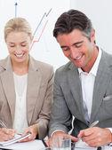 Alegre negocio escribiendo notas en una reunión — Foto de Stock