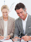 Cheerful business writting notes in a meeting — Stock Photo
