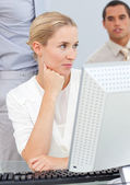 Pensive blond woman working at a computer — Stockfoto