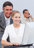 Smiling business team working at a computer — Stock Photo