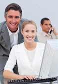 Confident business team working at a computer — Stock Photo