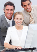 Positive business team working at a computer — Stock Photo