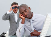 Afro-american businessman annoyed by a man looking through binoc — Stock Photo