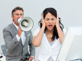 Furious manager shouting through a megaphone in a colleague's ea — Stock Photo