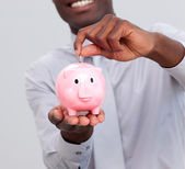 Afro-American businessman saving money in a piggybank — Stock Photo