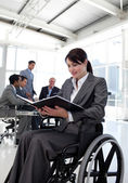 Businesswoman in a wheelchair reading a report — Stock Photo