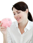 Attractive businesswoman looking at a piggybank — Stock Photo