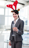Smiling businesswoman with a novelty Christmas hat toasting with — Stock Photo